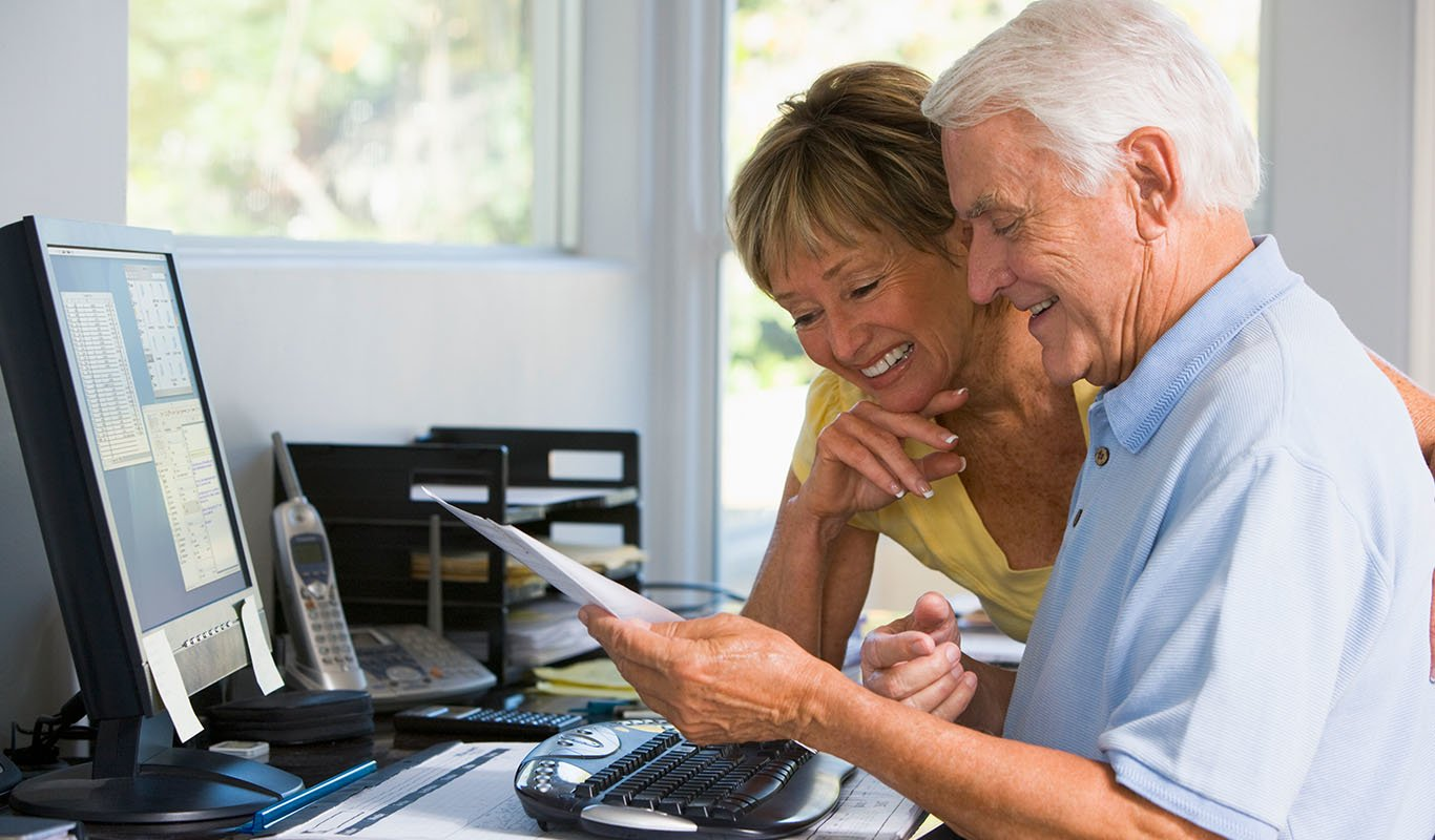 Senior couple smiling while reading a pamphlet at in their den in front of their computer