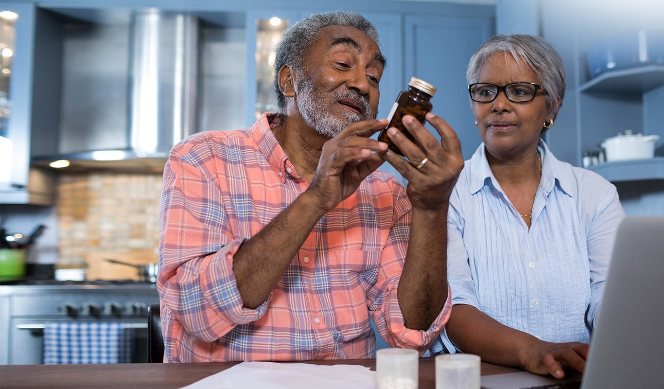 Senior adult couple at their kitchen table reading a pill bottle with a laptop and papers scattered around them