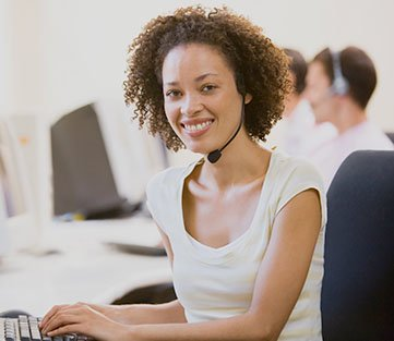 A young, bright, smiling woman sitting at a computer with a headset on.