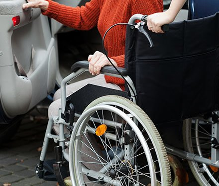 Woman in a wheelchair getting into a car