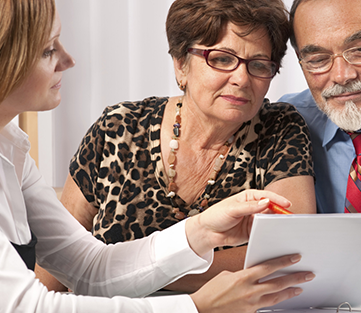 Senior adult couple being shown paperwork by a consultant